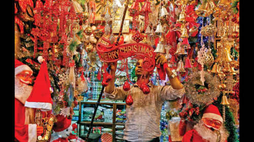 A vendor hangs decorative items in front of his shop ahead of Christmas in Kolkata, on 17 December 2018. REUTERS