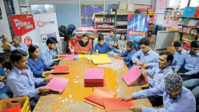 Visually-impaired at members of the Blind Relief Association making paper bags for the seven-day Diwali Bazaar.