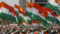 Supporters hold party flags during an election campaign rally by India's ruling Congress party president Gandhi in Mumbai